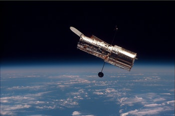 An image of the Hubble Space Telescope over Earth