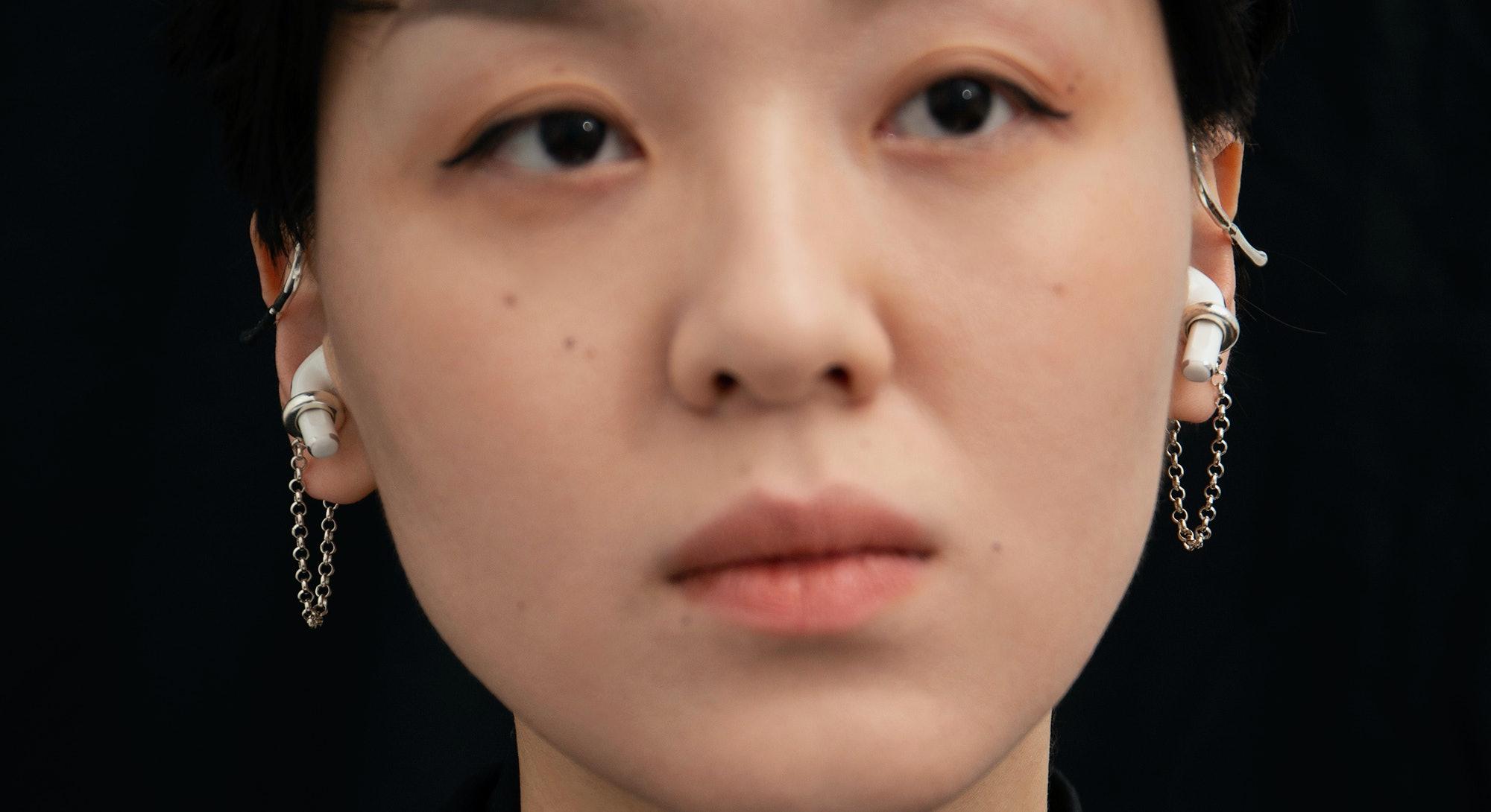A model is seen wearing a pair of Mara Paris AirPod earbud cuffs.