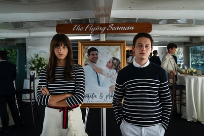 Chloe East and Uly Schlesinger in Generation, each wearing matching striped outfits and standing in front of a picture of a couple. She has her arms folded, he has his hands in her pockets.