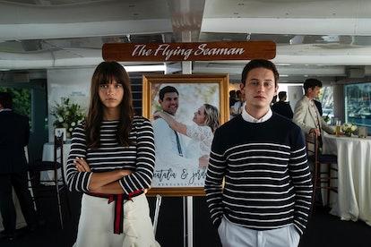 Chloe East y Uly Schlesinger en Generation, cada una con trajes a rayas a juego y de pie frente a una foto de una pareja.  Ella tiene los brazos cruzados, él tiene las manos en los bolsillos.