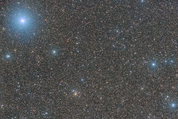an image of a starfield with some bright, blue stars standing out