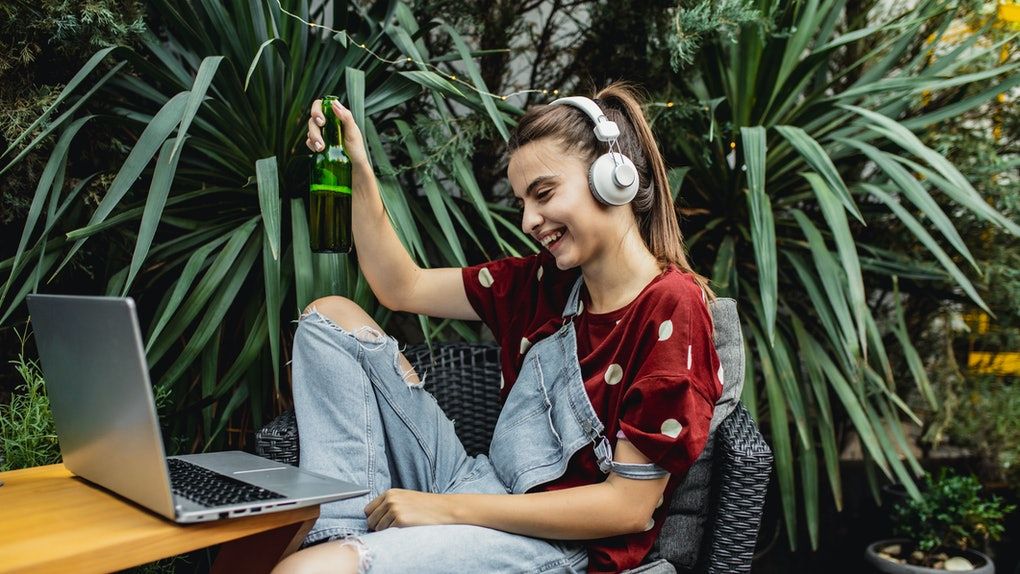 A young woman laughs while holding a beer and attending a virtual St. Patrick's Day party with games and her long-distance BFFs.