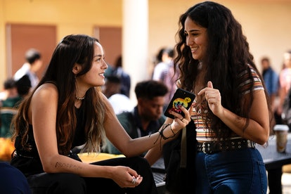 Chase Sui Wonders and Haley Sanchez in a still from Generation. The two girls are talking to each other, the left one sitting on the table and showing the right one her phone. The right one is standing and smiling at the other.