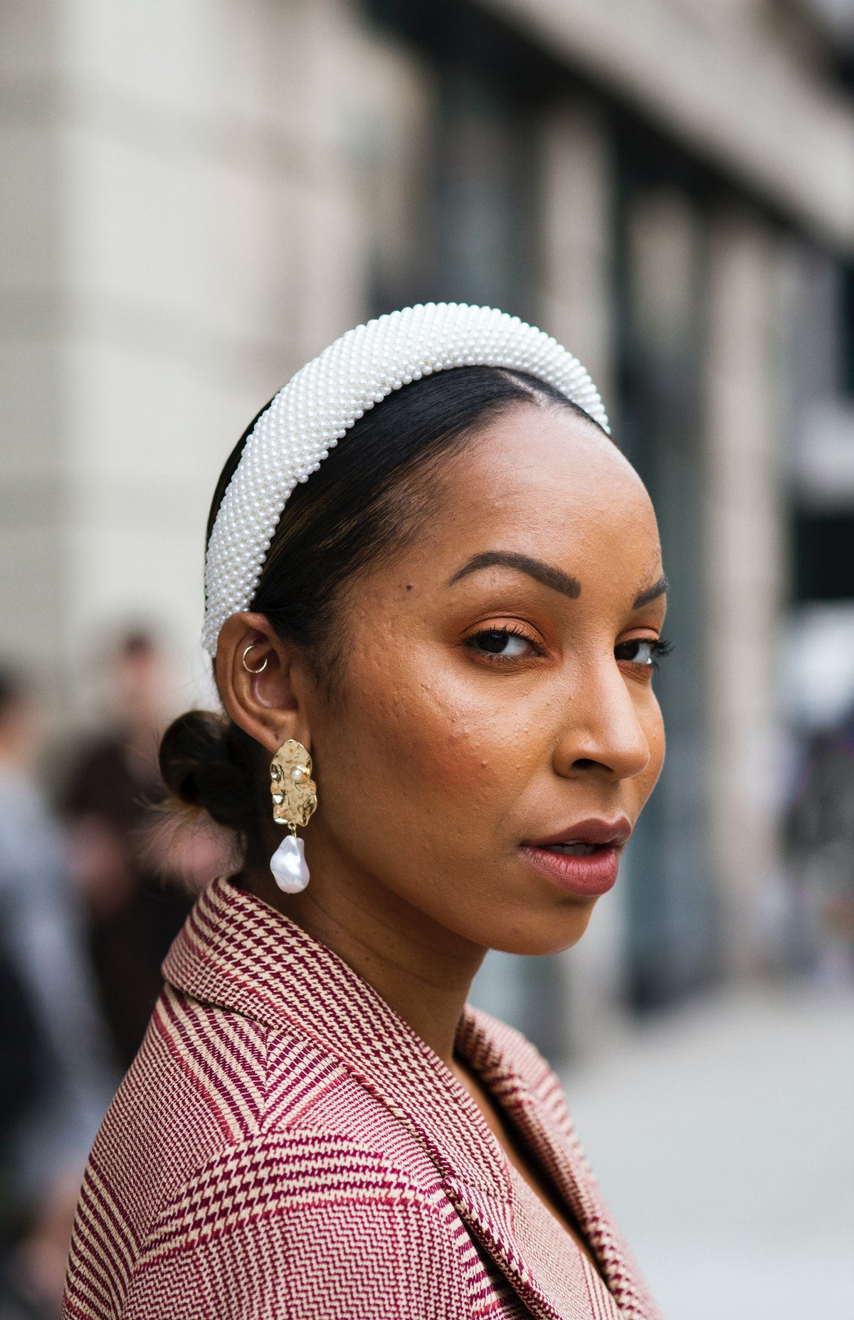 Guest wearing red and white checked blazer and oversized pearl Alice band headband is seen during Ne...