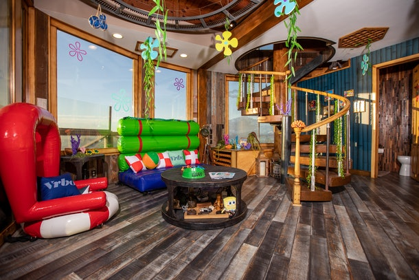 The interior of SpongeBob's pineapple home on Vrbo includes the iconic living room furniture and cartoon flowers.