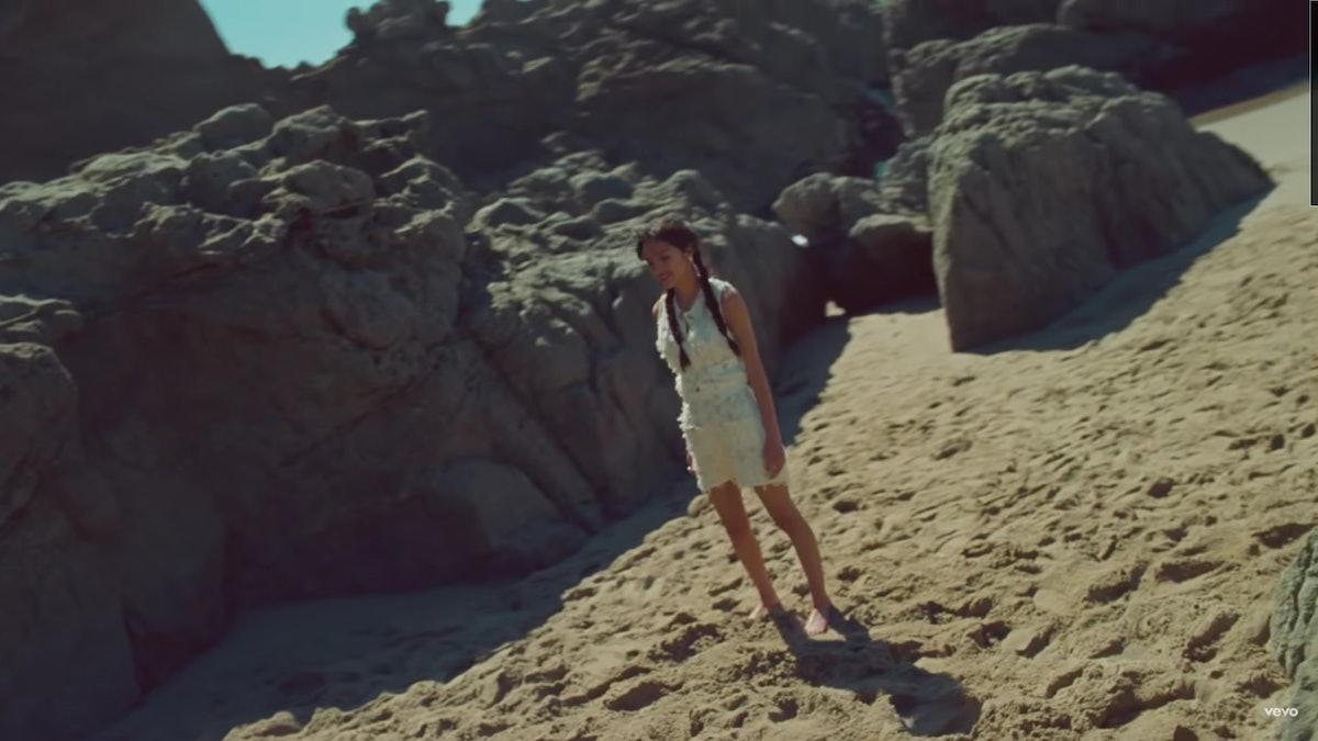 "Olivia Rodrigo on the beach in the ""Deja Vu"" music video."