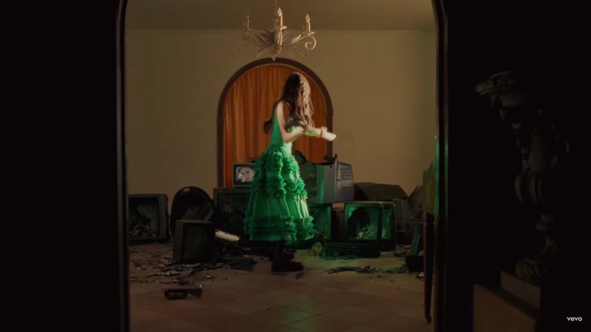 "Olivia Rodrigo smashing TVs in a green dress for the ""Deja Vu"" music video."