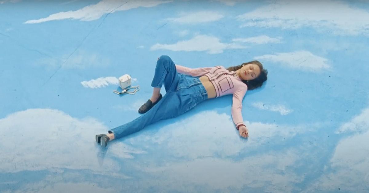 "Olivia Rodrigo lays on a sea of clouds in the music video for ""deja vu."""