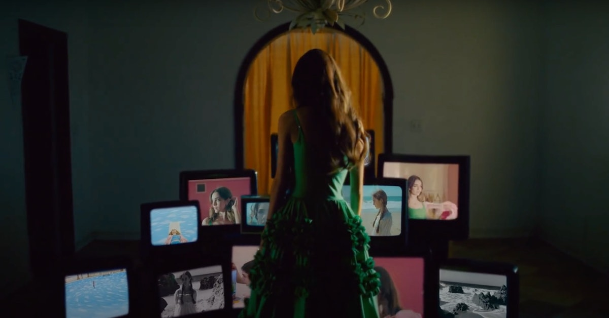 """Olivia Rodrigo poses in front of a stack of televisions in the music video for """"deja vu."""""""