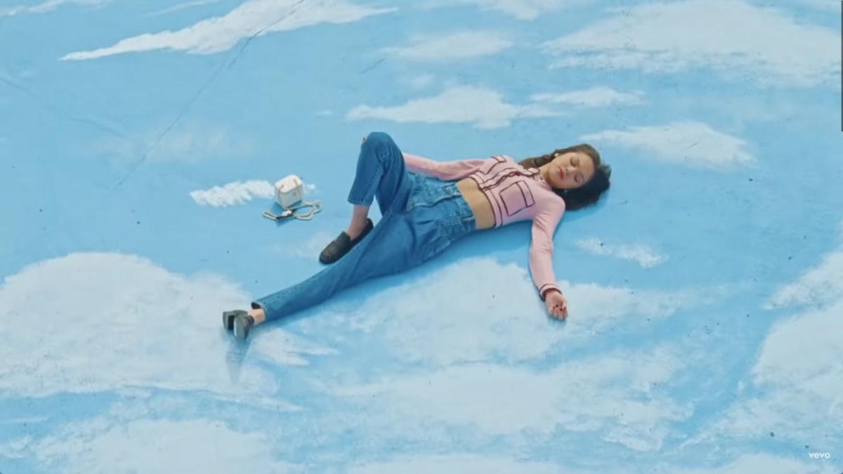 "Olivia Rodrigo laying in the sky in the ""Deja Vu"" music video."
