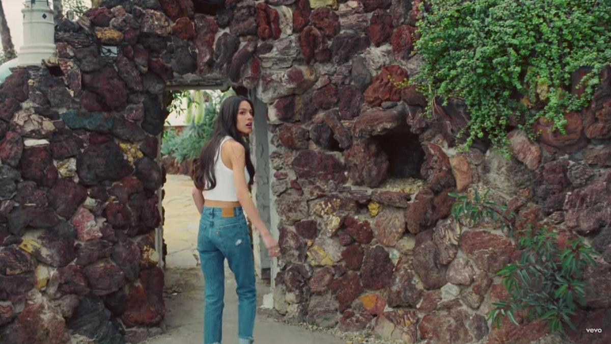 """Olivia Rodrigo in jeans and a tank top in the """"Deja Vu"""" music video."""