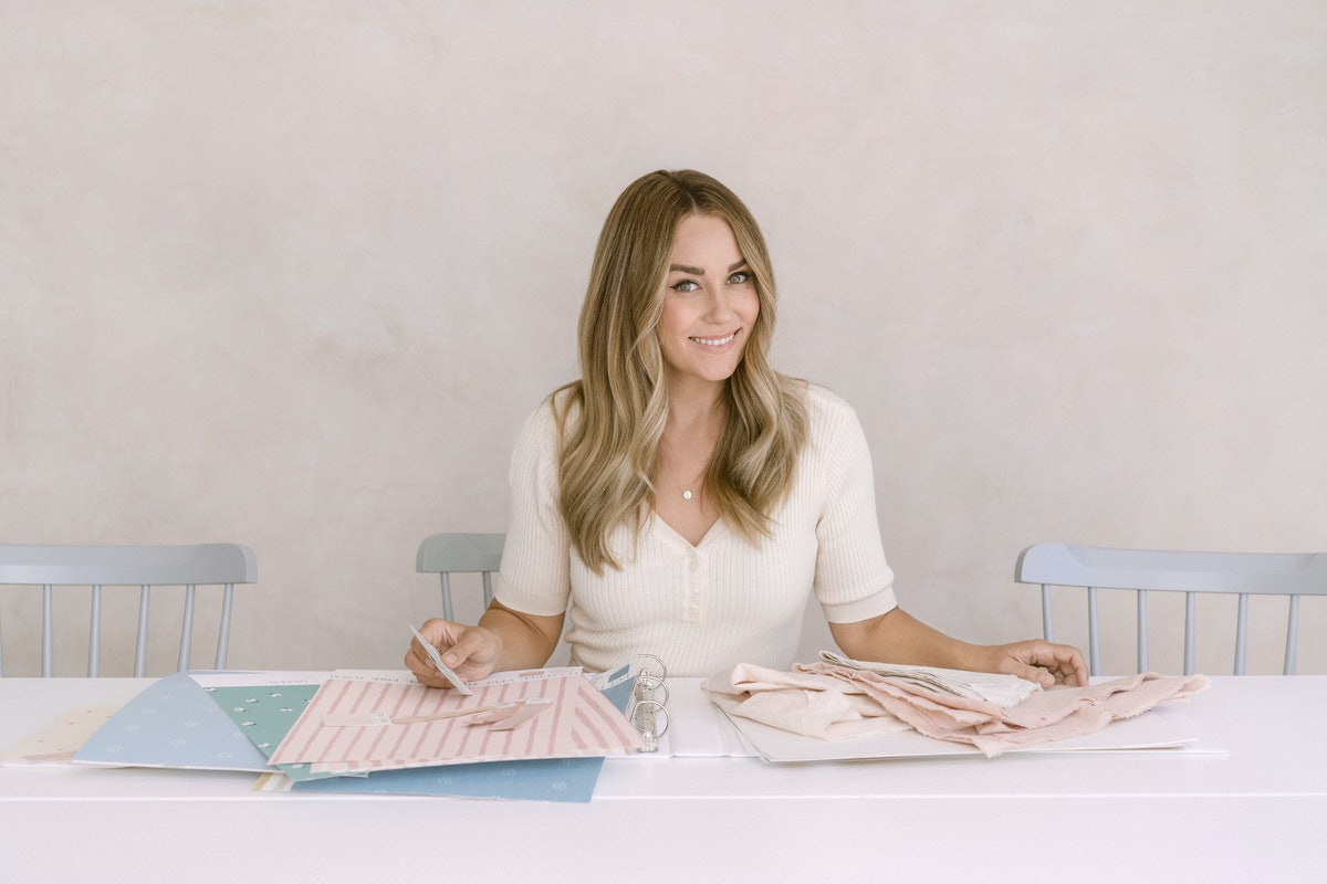 Lauren Conrad sits at a table looking at swatches for Amazon Handmade.