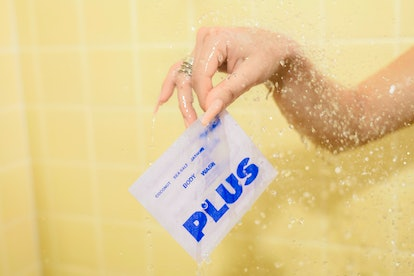 a hand in a shower holds out a white package of plus