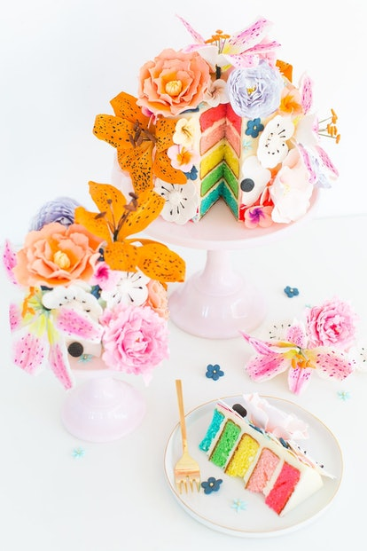 rainbow layer cake topped with sugar flowers