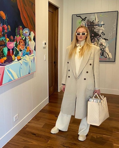 Sophie Turner wearing a trench coat and white trousers.
