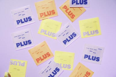 A selection of PLUS packages are laid out against a purple backdrop