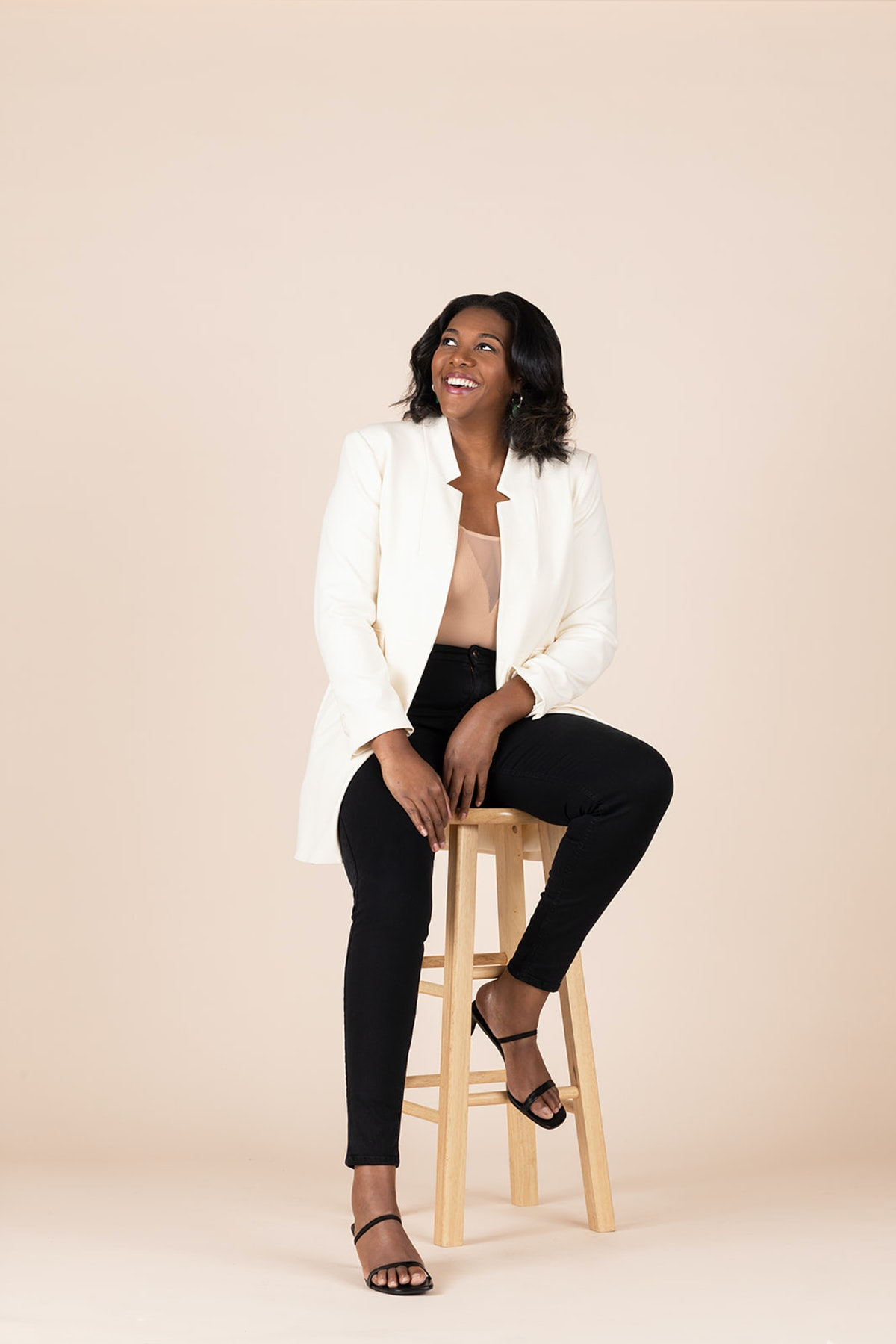 Founder of Glory Skincare Alisia Ford sits on a stool.