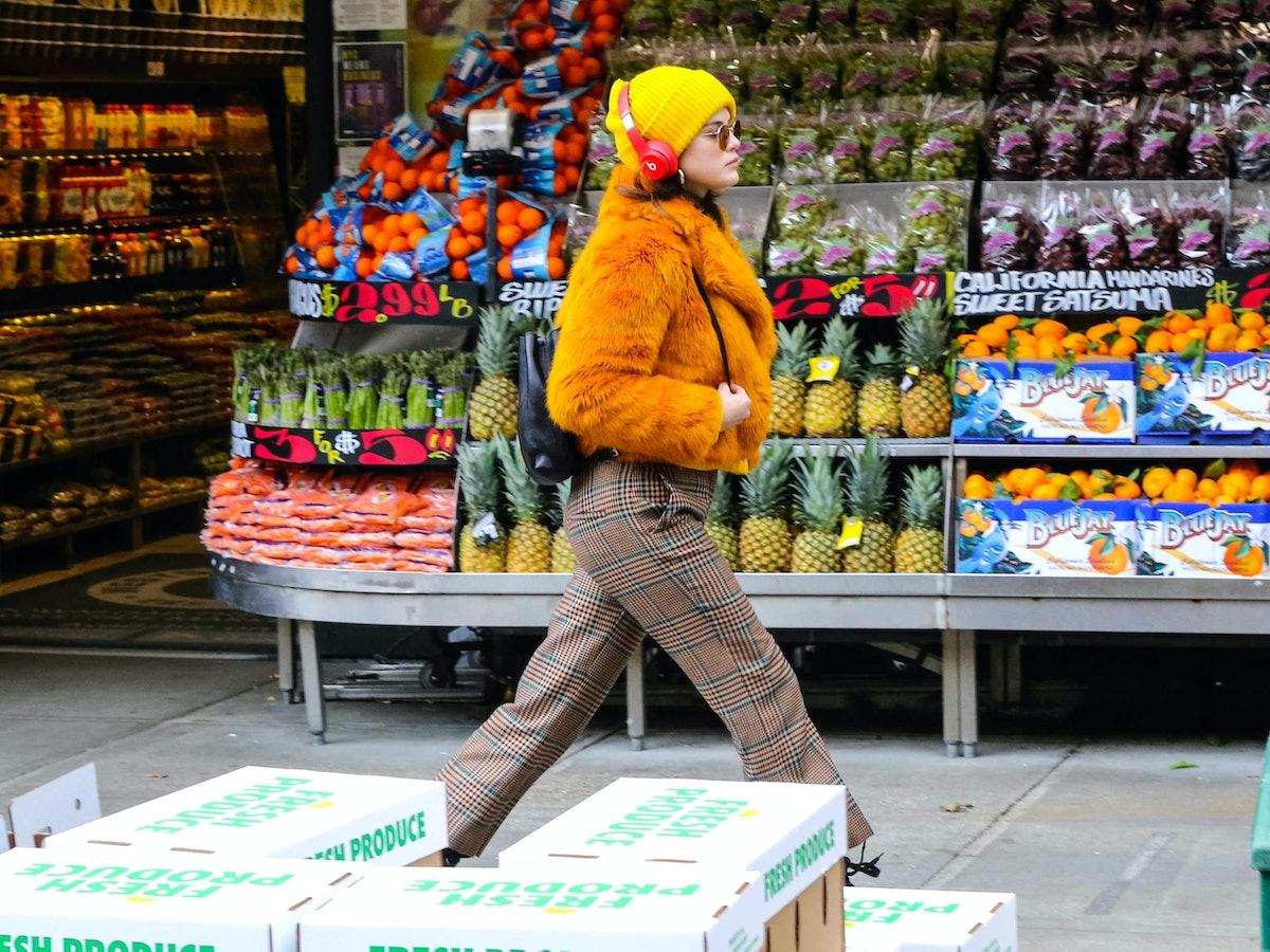Selena Gomez wearing an orange coat