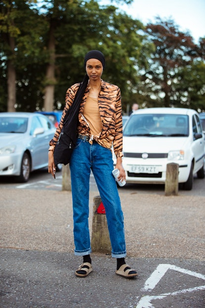 Model Ugbad Abdi wears a black headscarf, tiger print shirt, blue jeans, black socks, and brown Birkenstock sandals after the Simone Rocha show during London Fashion Week September 2019 on September 15, 2019 in London, England.