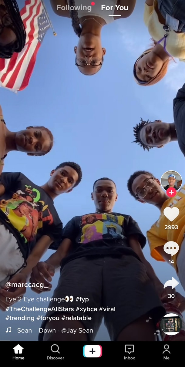 A group of friends plays the eye-to-eye challenge on TikTok while hanging outside on a sunny day.