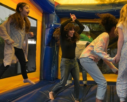 "Karla Souza is jumping in a bounce house with several kids in an episode of HOME ECONOMICS called ""Bounce House Rental."""
