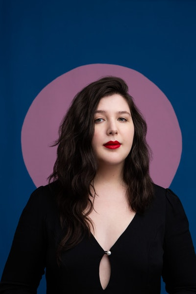 A portrait of Lucy Dacus. She stands in front of a blue background with a lavender circle framing her head. She's wearing red lipstick and a buttoned black top.