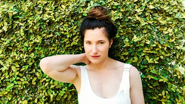 Kathryn Hahn in white overalls standing in front of a hedge, with her hair in a topknot