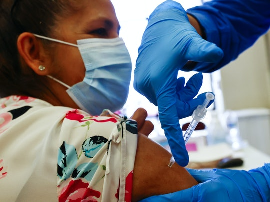 APPLE VALLEY, CALIFORNIA - MARCH 30: A woman receives a dose of a COVID-19 vaccine at a vaccination clinic hosted by Providence St. Mary Medical Center on March 30, 2021 in Apple Valley, California. The hospital was treating over 180 COVID-19 patients at the peak of the surge but has seen a sharp decline and is currently caring for just 12 coronavirus patients while also hosting the vaccination clinic at a nearby church. In addition, the hospital is now able to receive one visitor per patient, with restrictions and exceptions, during visiting hours. (Photo by Mario Tama/Getty Images)