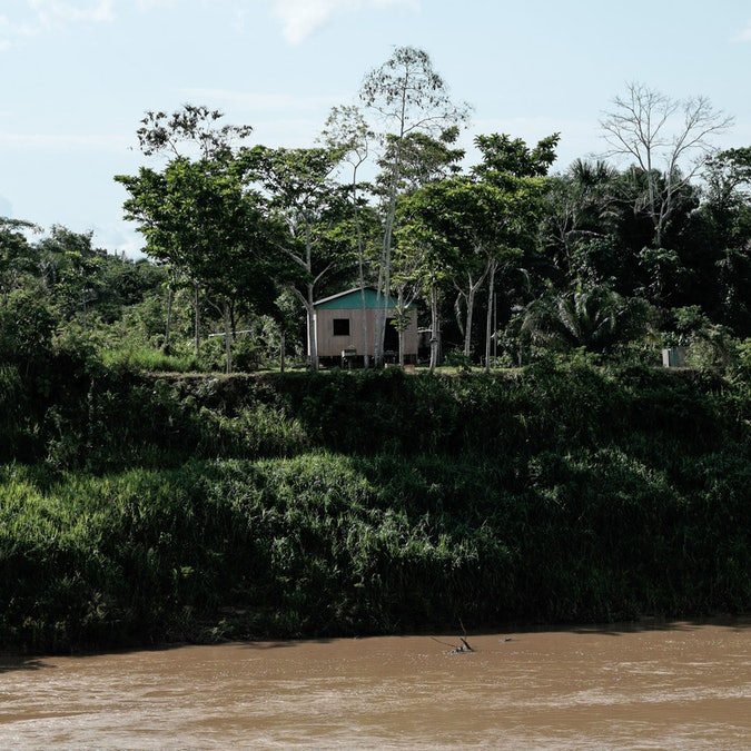 A small house sits on a riverbank in the state of Acre in Brazil.