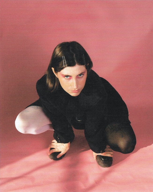 A portrait of Ian Sweet. She's kneeling against a pink background with rosy eyeshadow on, and an all-black outfit.