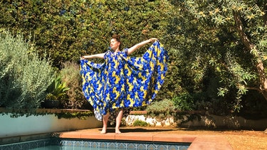 Kathryn Hahn in a big, flowing blue and yellow dress, that she holds up in the air like wings