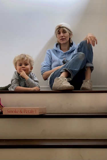 Mickey Sumner and her son, Akira, sitting on the floor at the top of a set of stairs
