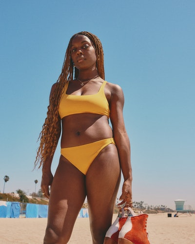 Model wearing yellow swimsuit from Everlane's first swimwear collection.