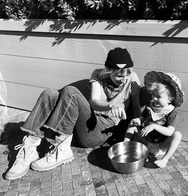 a black-and-white photo of Mickey Sumner with her son, Akira, sitting outside, playing with a bowl of water