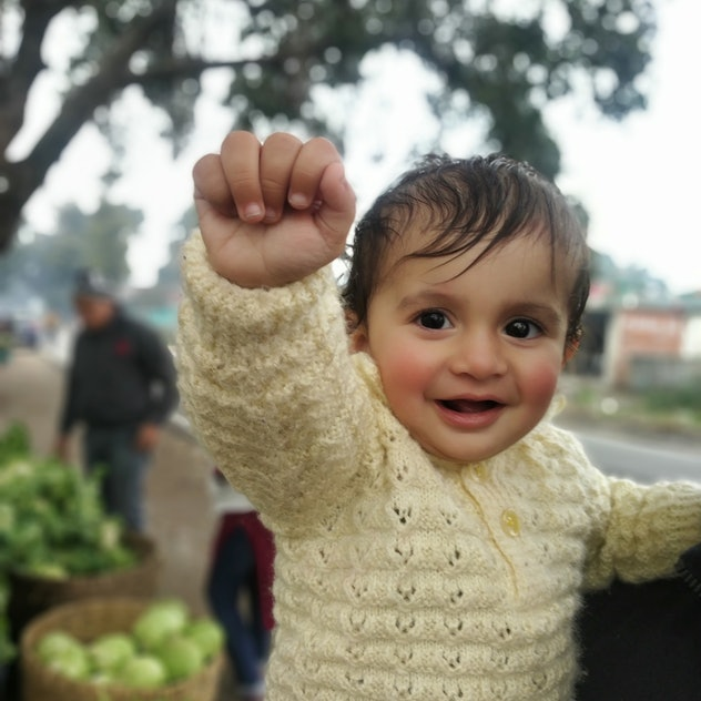 baby smiling, holding up his fist