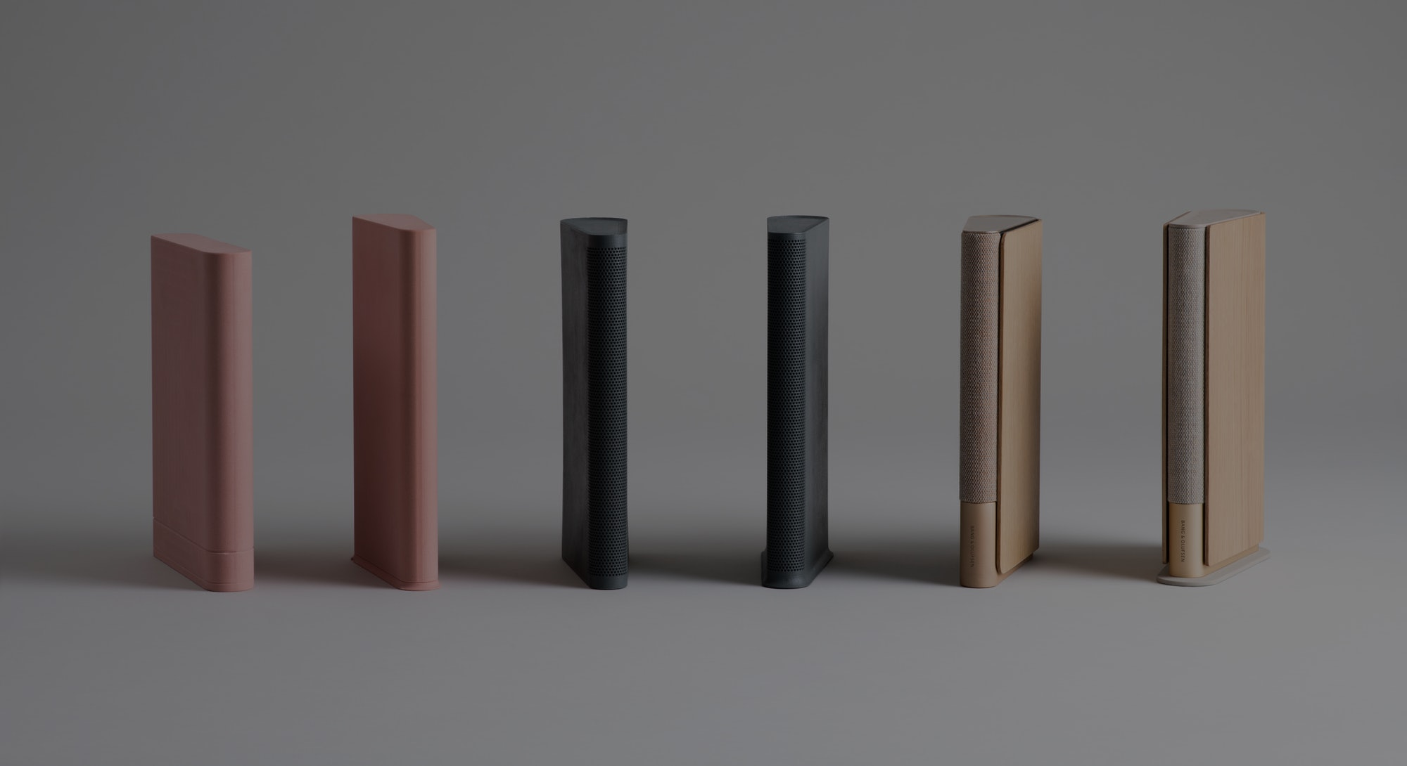 Lean speakers in golden and black tones by Bang and Olufsen. The pink ones are size models.