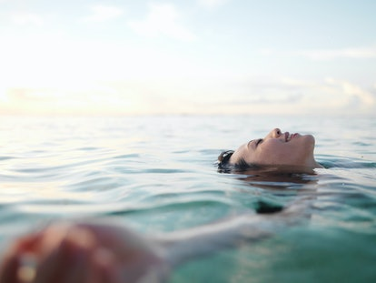 Woman floating in sea, smiling