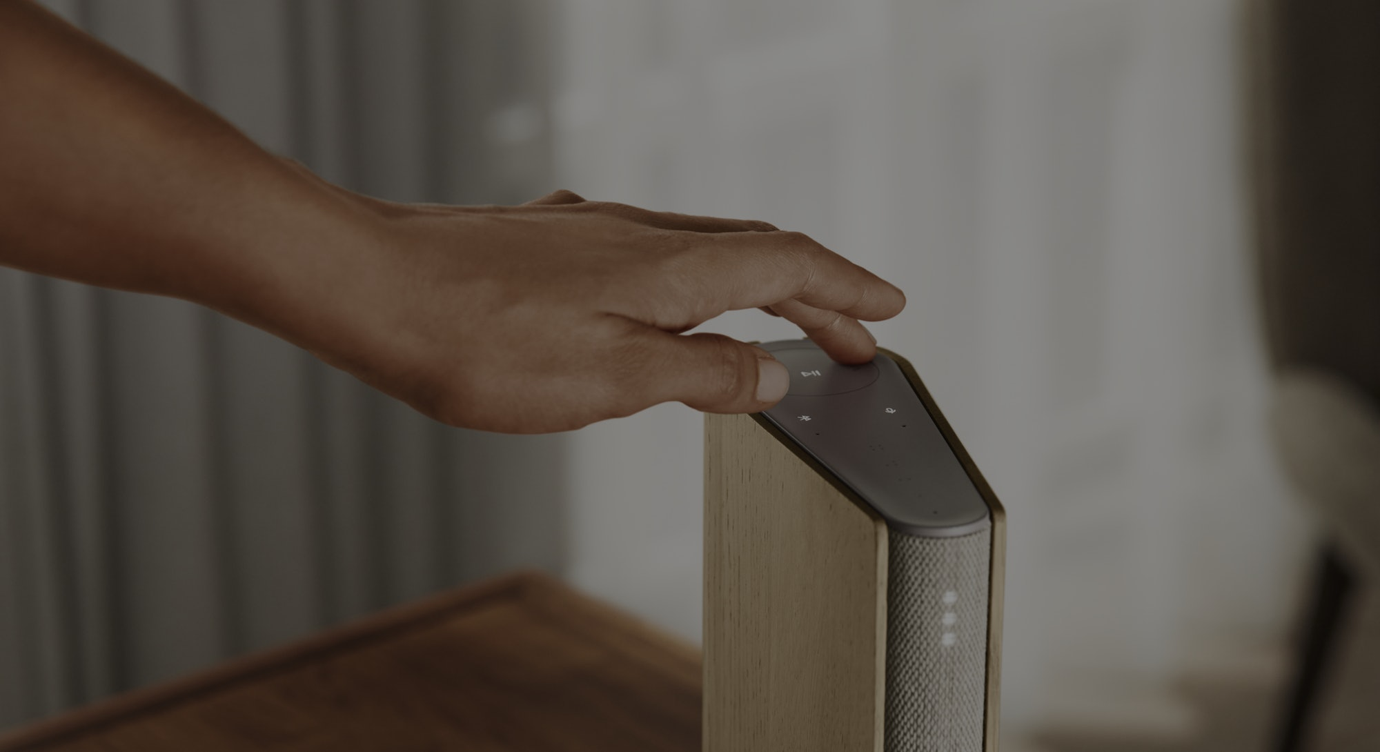 A hand is touching a compact Bang and Olufsen Emerge speaker.