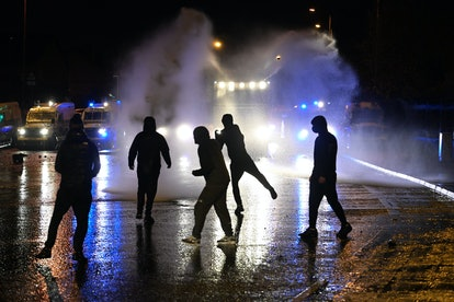 Nationalists attack police vehicles as they deploy water canons on Springfield Road on April 8, 20...