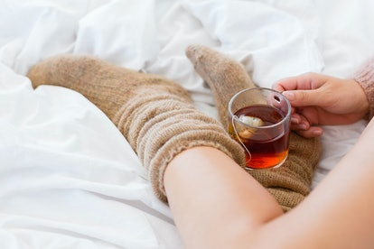 Close-up of a woman with cup of herbal tea in bed