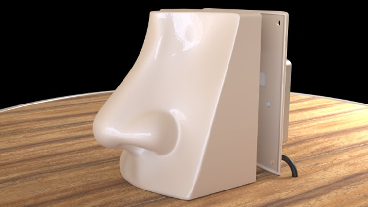 A fake nose powered by AI is seen on a desk surface. The nose is beige.