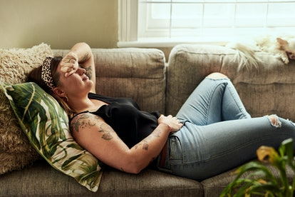 Young woman suffering from stomach cramps on the sofa at home