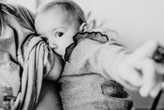 Black and white photo of a breastfeeding baby looking at the viewer