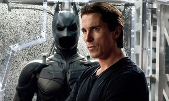 Christian Bale as Bruce Wayne by his batsuit in The Dark Knight