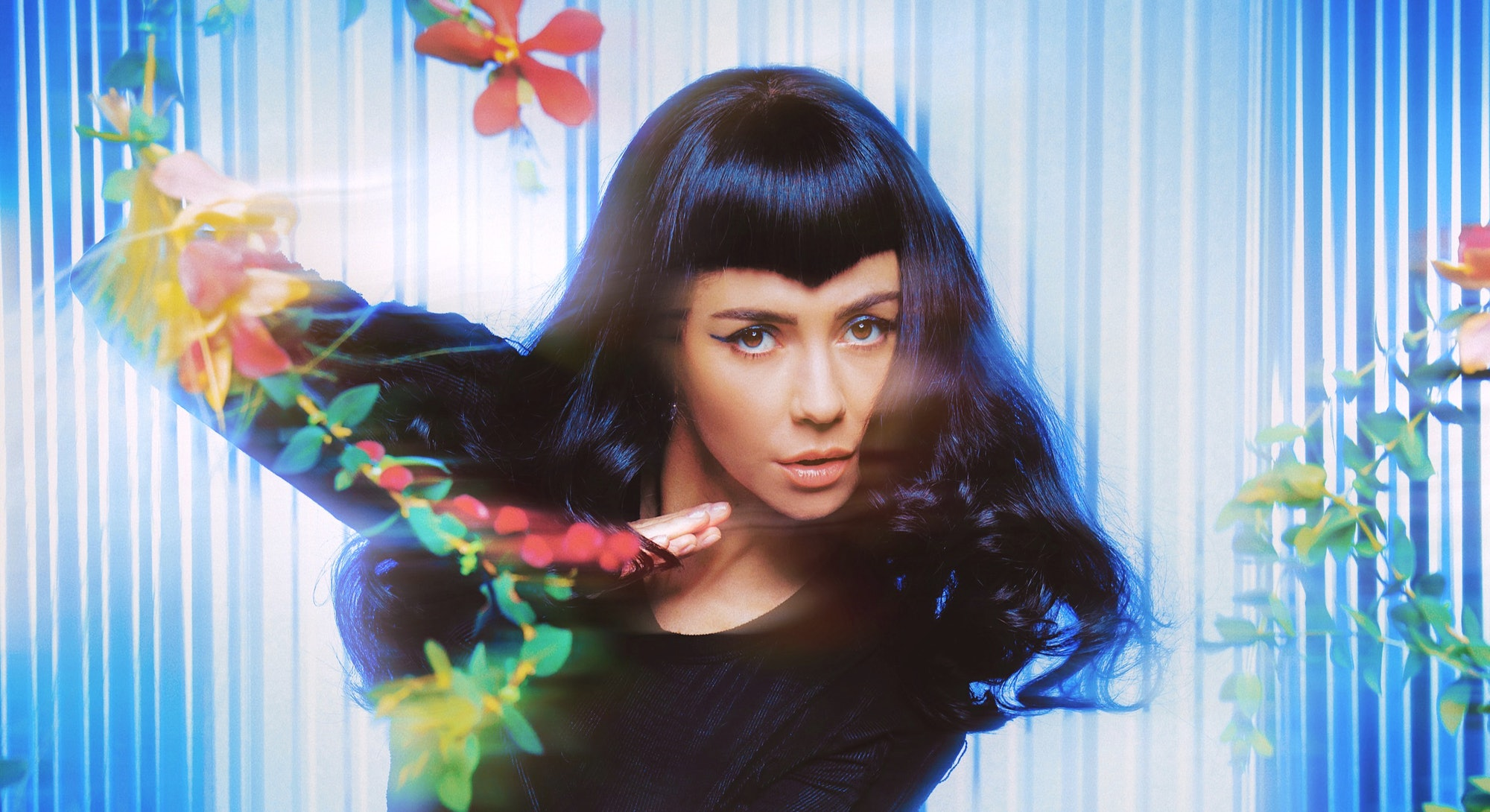 A photo of MARINA. She's in a black outfit and standing against a cyber blue background with tropical flowers.