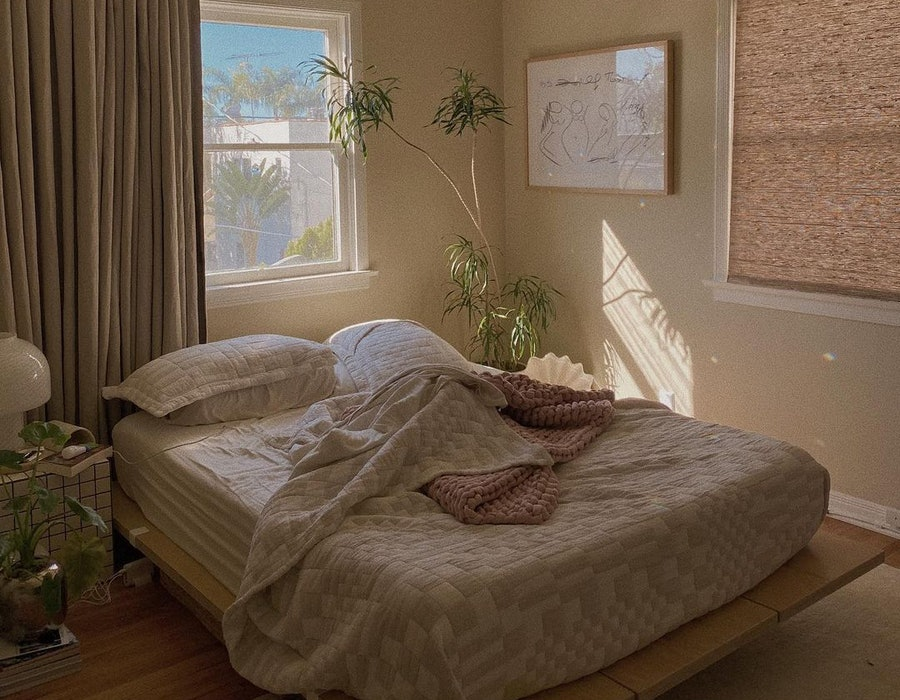 A bed with a geometric comforter against a window with the blinds drawn.