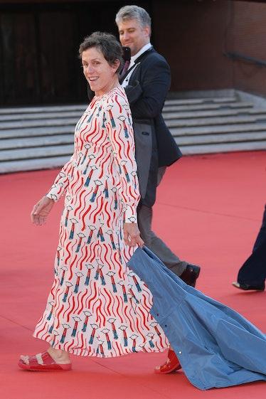 Frances McDormand carrying a blue jacket
