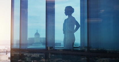 Businesswoman looking thoughtful while looking out a window
