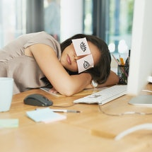 Shot of a tired businesswoman napping at her desk with adhesive notes on her eyes