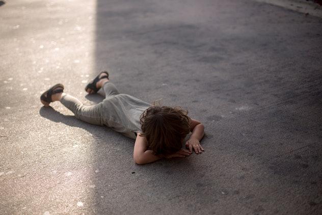 child having a tantrum on the sidewalk